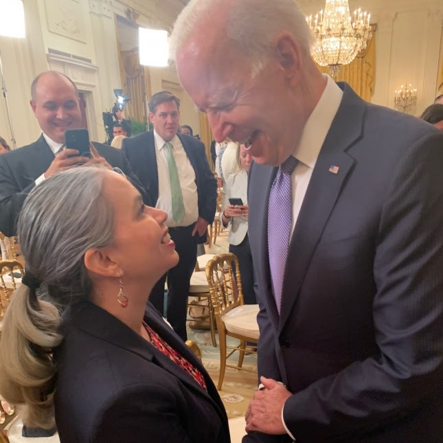 Policy Manager Olivia Garcia looking up smiling at President Biden who is greeting her