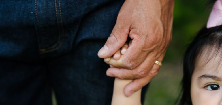 close up of Latino fathers hand holding toddler daughters hand