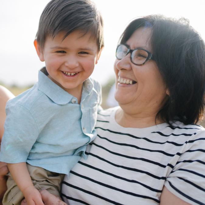 Latina grandmother smiling and holding smiling young grandson