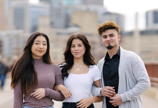 Two Latina young women and a Latino young man with link arms and cityscape in background