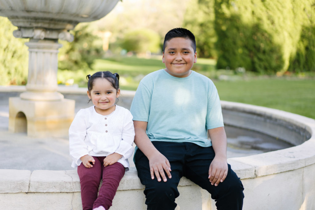 Smiling toddler girl and her older brother sitting on the edge of a fountain in a park