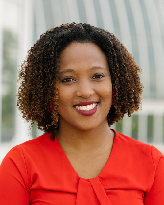 Afro latina woman in red shirt smiling