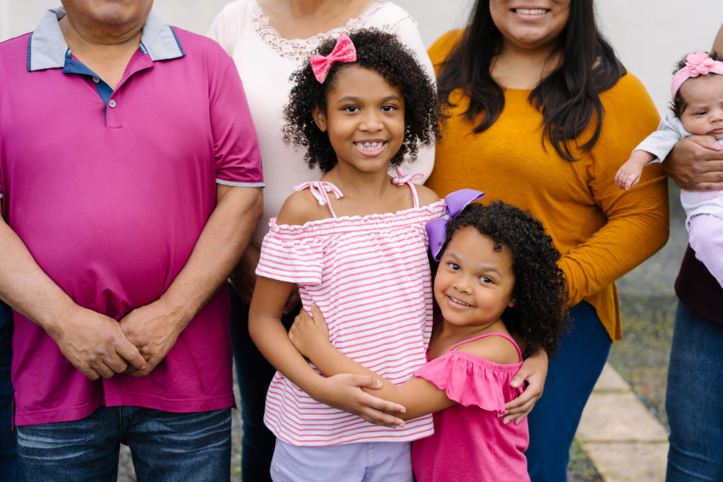 Ninas, Two young afro latina sisters smilng and hugging with family behind them